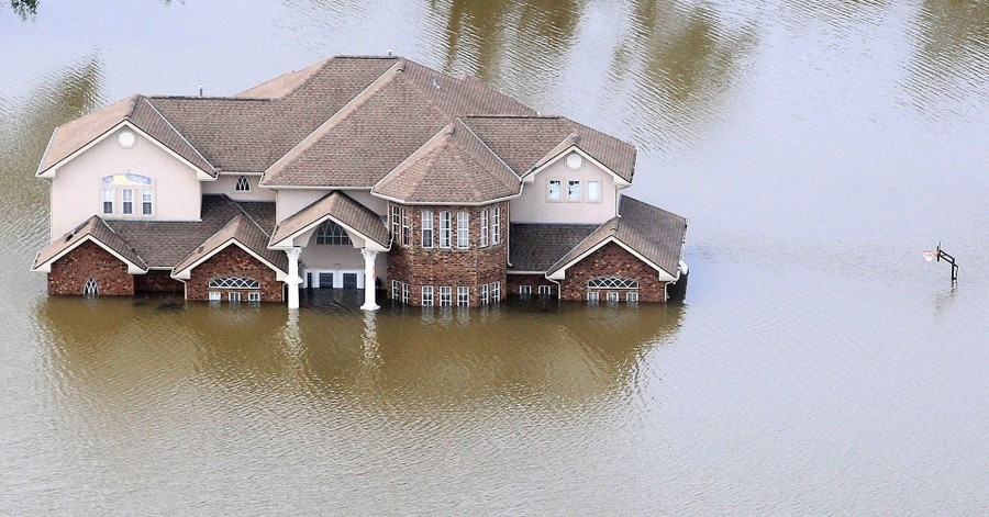 an aerial drone picture of a house in Houston after Hurricane Harvey sitting underwater. Water is coming up almost to the top of the front door