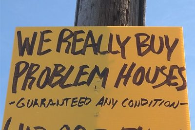 a yellow we buy houses sign stapled to a telephone pole.